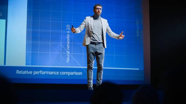 manliga högtalare står på scenen och gör presentation av den tekniska produkten, visar infographics, statistik animation på skärmen. live event / device release / start-up konferens - graphs animation bildbanksfoton och bilder