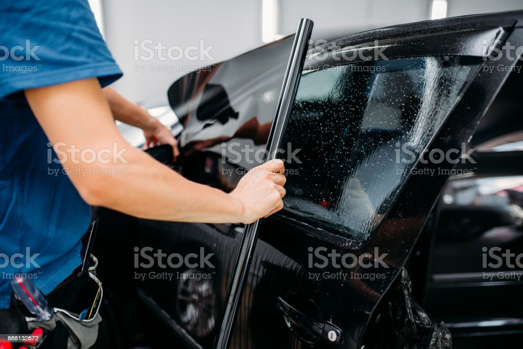 Male specialist applying car tinting film stock photo