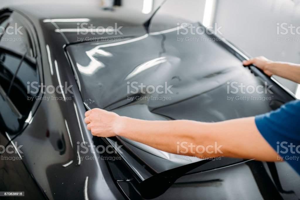 Male specialist with car tinting film in hands stock photo
