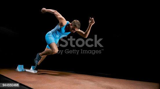 istock Male sprinter leaving starting blocks 944550468