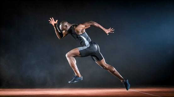 Male sprinter running on track at night.