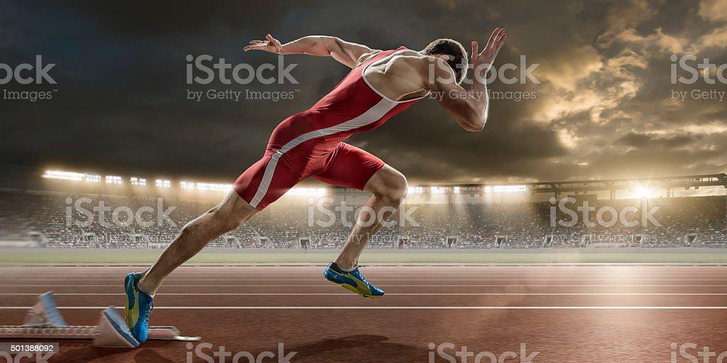 Masculino corredor de Sprint comienza desde cuadras en el estadio de atletismo - foto de stock