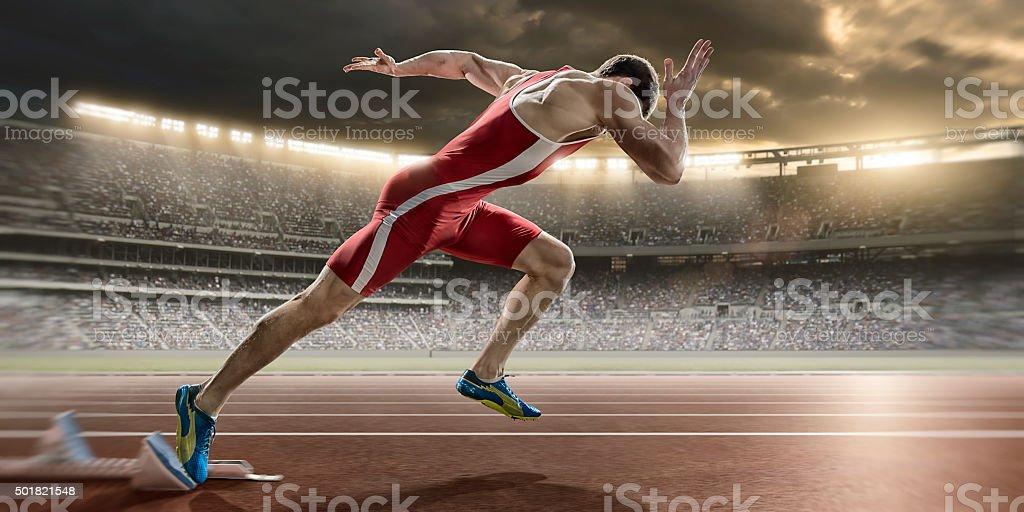 Male Sprinter Sprint Starts From Blocks in Athletics Stadium stock photo