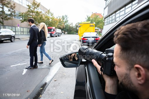 istock Male Spy Taking Photograph Of A Couple Walking On Street 1179125191