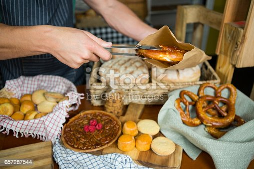 istock Male staff packing pretzel in paper bag 657287544