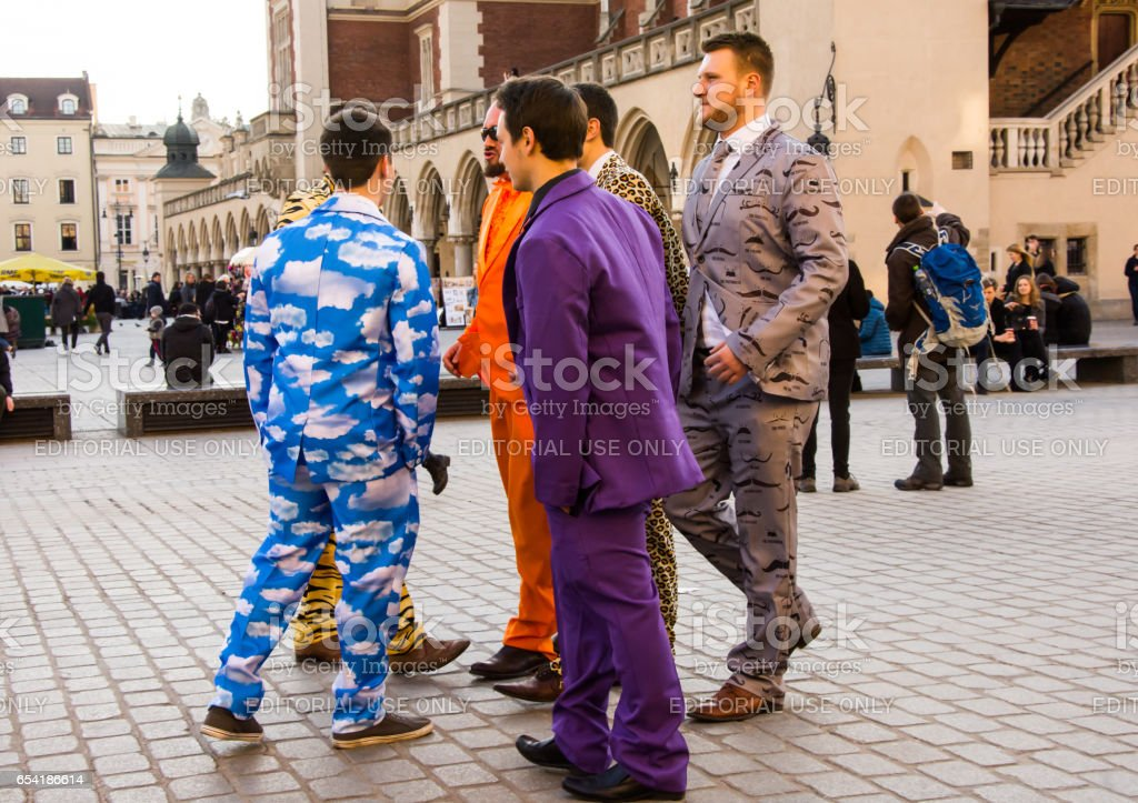 Male stag party in brightly coloured clothing, Krakow, Poland. stock photo