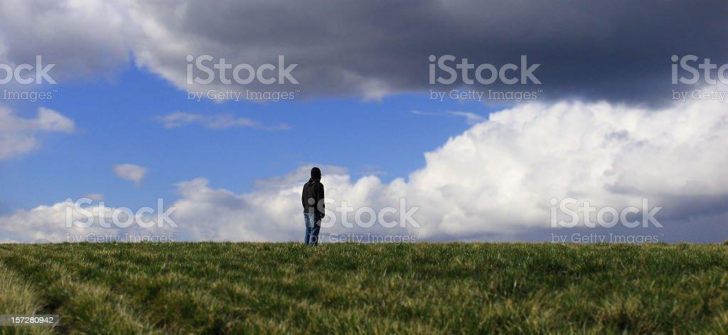 Male Standing Alone in Dark Field royalty-free stock photo