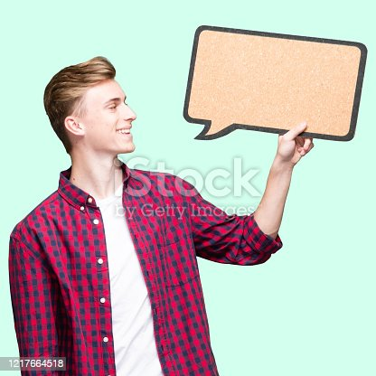 Waist up of aged 16-17 years old with brown hair male standing wearing shirt who is contemplating who is showing with hand and holding speech bubble with copy space