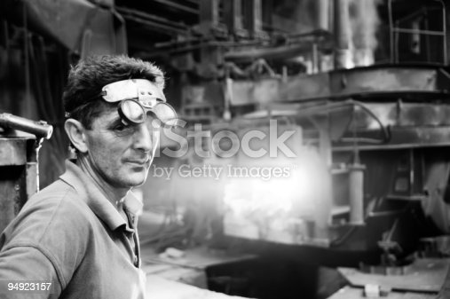Worker standing in front of the electric arc furnace in steel mill. Black and white conversion.