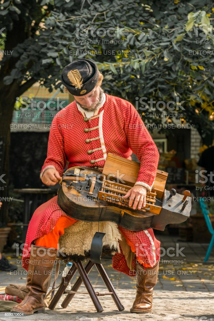 Male street artist in Budapest playing an old instrument wearing red traditional clothes. royalty-free stock photo