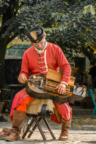 Male street artist in Budapest playing an old instrument wearing red traditional clothes. stock photo