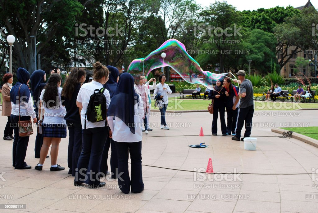 Male street artist makes big soap bubbles with two sticks and thread for group of women in Hyde Park stock photo