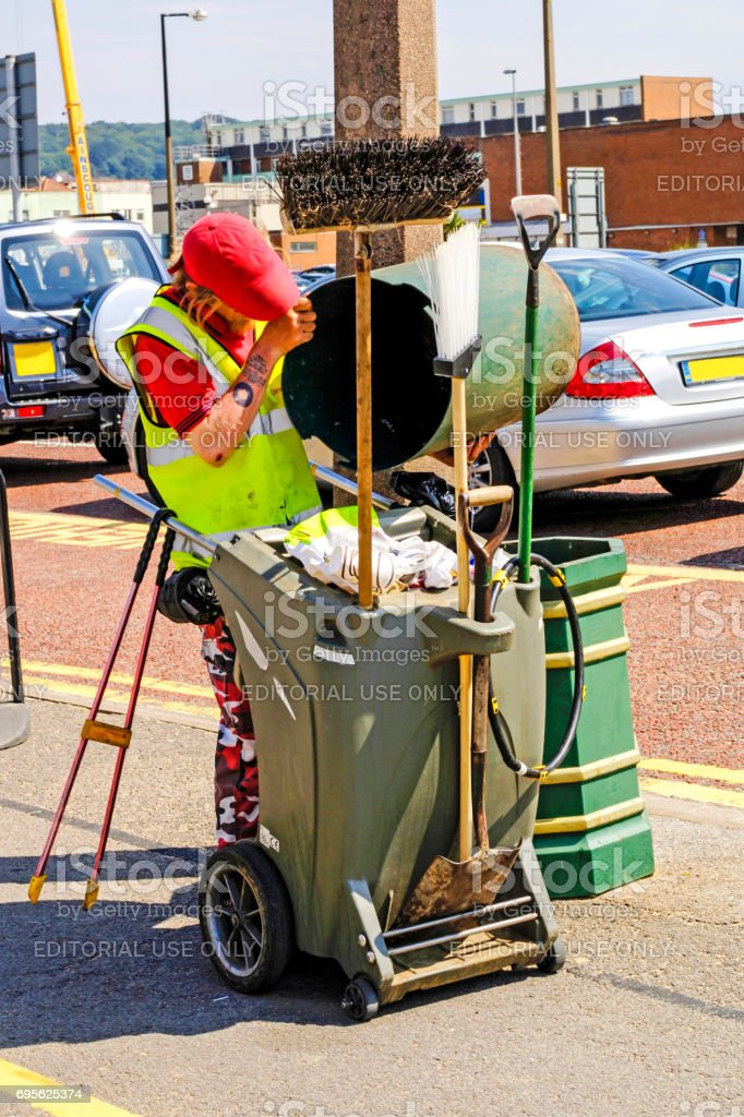 Male street cleaner empty a public trash can in Weston-Super-Mare, Somerset UK stock photo