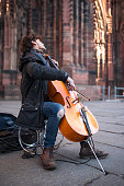 Strasbourg, France - February 07, 2020: Male street musician playing cello with Cathedral in background
