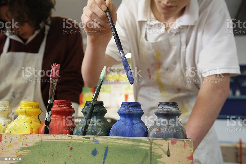 Male student (15-17) dipping brush into paint bottle, mid section royalty-free stock photo