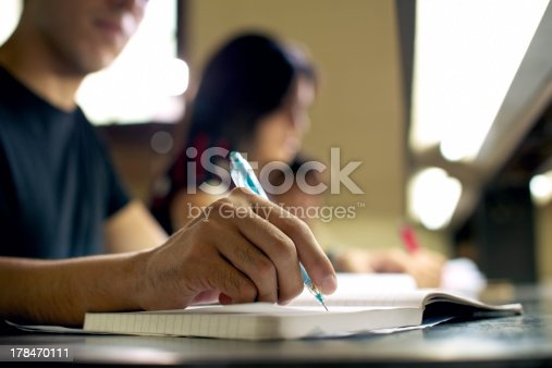 istock Male student doing homework at library 178470111