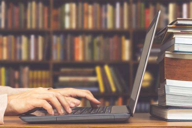 estudante do sexo masculino as mãos fazendo pesquisa no laptop e navegar a internet para preparar o exame e aprender lições na biblioteca - foto de acervo