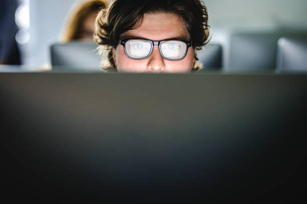 männliche schüler lernen einen vortrag über desktop-pc im computerraum. - starren stock-fotos und bilder