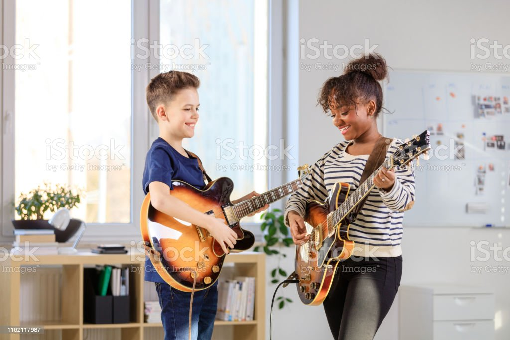 Male student learning guitar from trainer Boy playing electric guitar. Student is learning music from female guitarist. They are in training class at conservatory. 12-13 Years Stock Photo