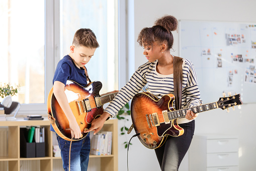 Male Student Learning Guitar From Trainer Stock Photo - Download Image Now