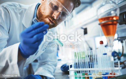 Male attractive student of chemistry working in laboratory