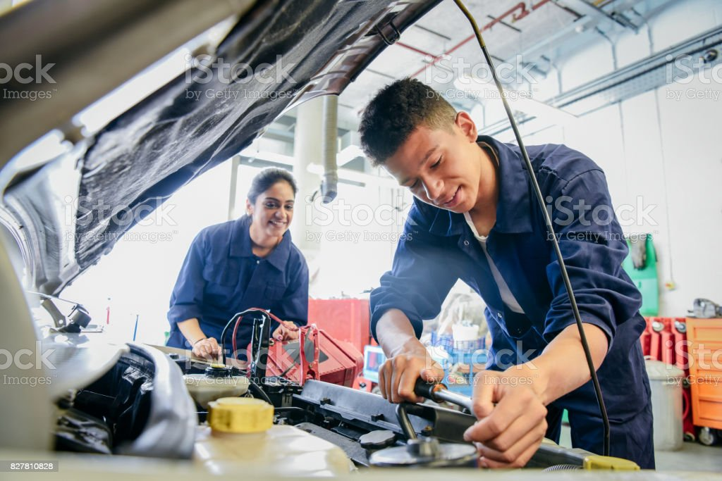 Male student repairing car, woman watching stock photo