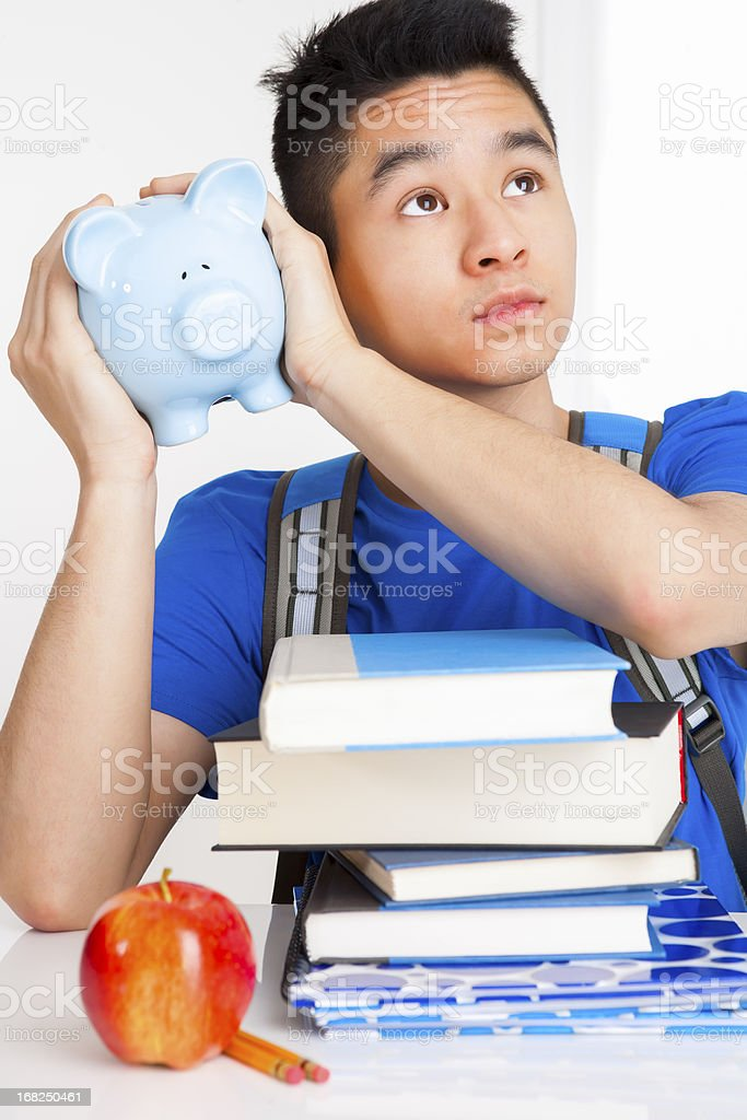 Male student shaking piggy bank royalty-free stock photo