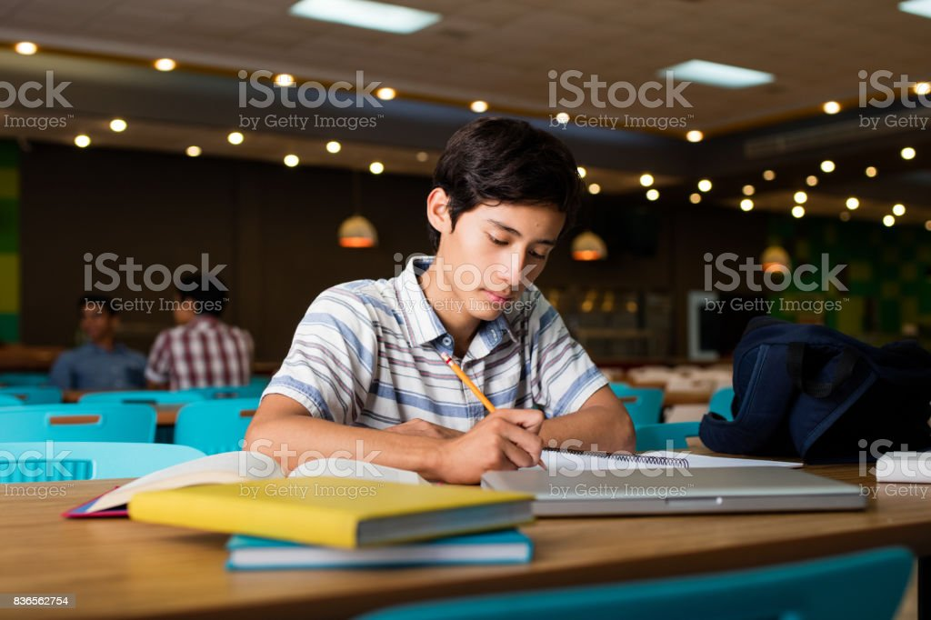 Male student sitting and writing stock photo