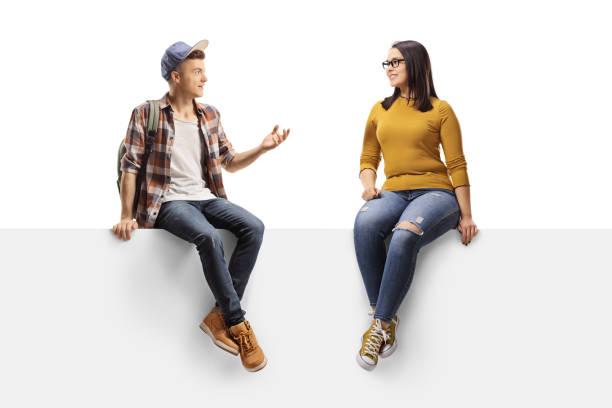 パネルに座って女友達と話す男子学生 - 談笑する ストックフォトと画像