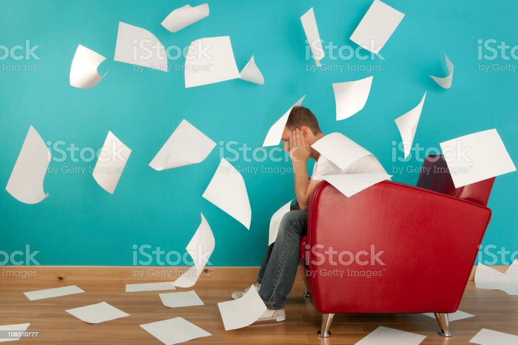 A male student sitting on a red armchair royalty-free stock photo