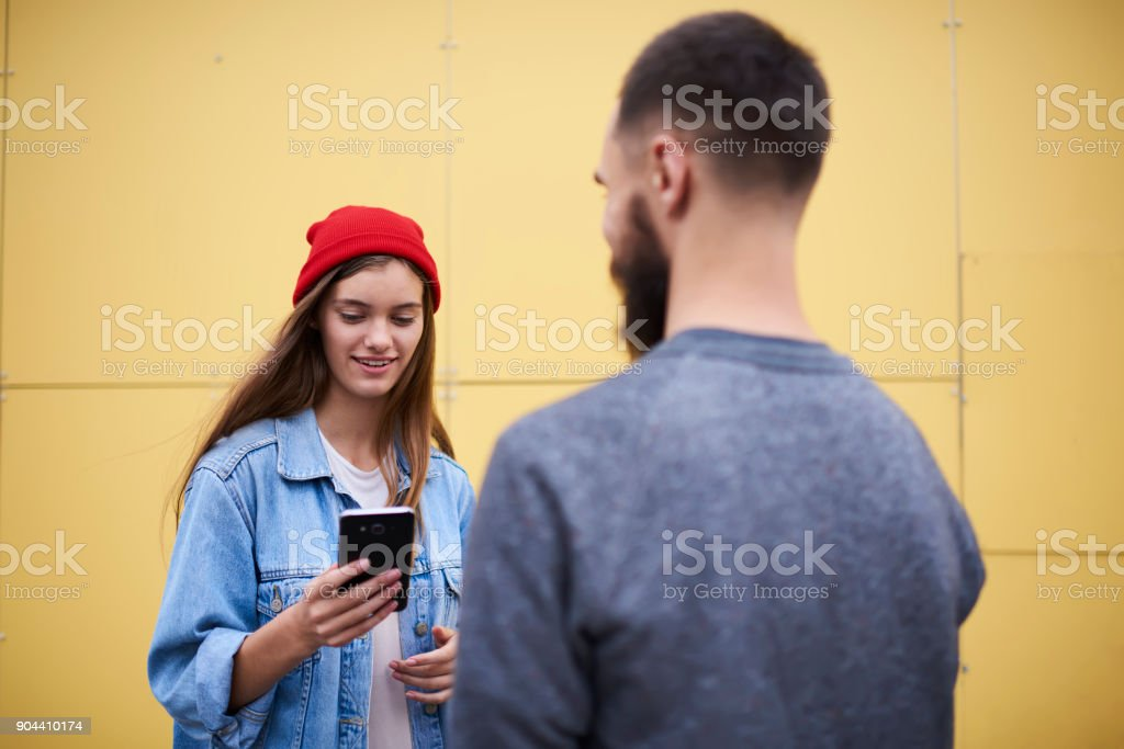 Male student standing near to positive young hipster girl sharing opinions about new software application on mobile phone. Female searching useful information via cell phone using internet connection - foto stock
