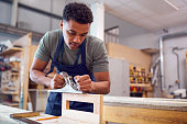 istock Male Student Studying For Carpentry Apprenticeship At College Using Wood Plane 1218972142