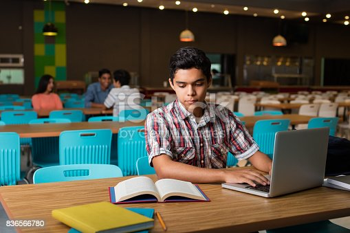 istock Male student typing on computer from book 836566780