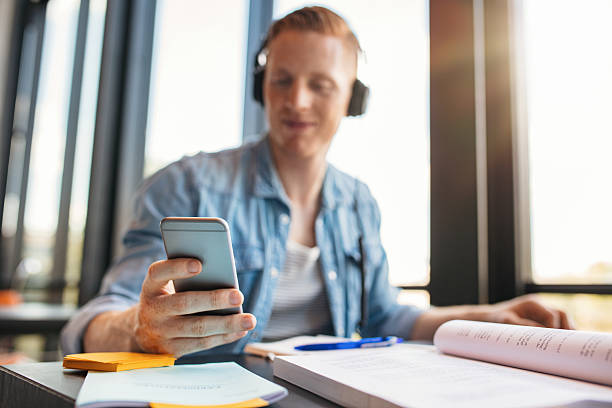 male student using mobile phone in a library - jacob ammentorp lund stock pictures, royalty-free photos & images