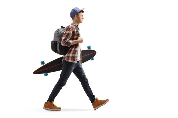 Male student walking and holding a longboard stock photo