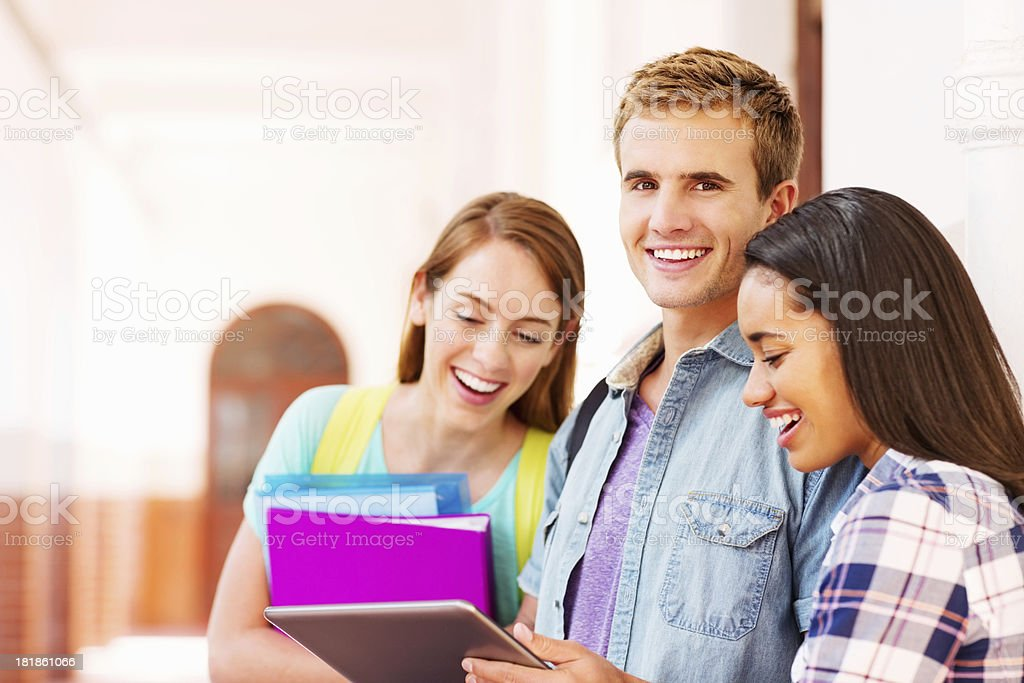 Male Student With Female Friends Using Digital Tablet On Campus royalty-free stock photo