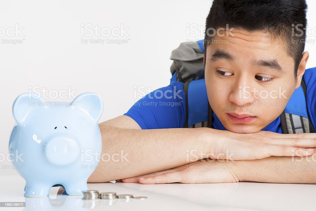 Male student with piggy bank stock photo