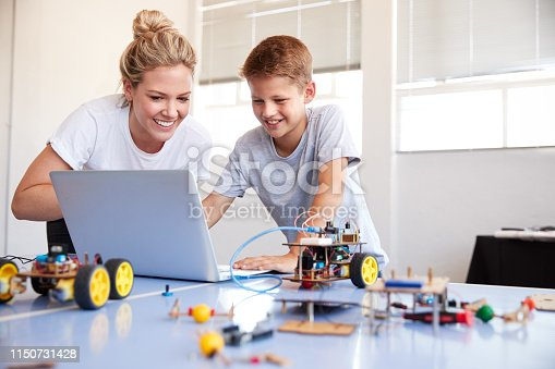 istock Male Student With Teacher Building Robot Vehicle In After School Computer Coding Class 1150731428