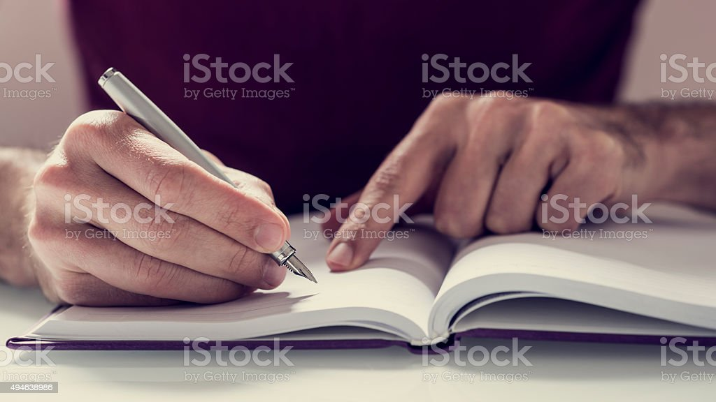 Male student writing notes with fountain pen in his notebook stock photo