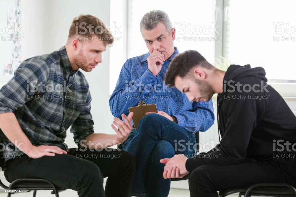 Male students discussing problems by therapist Social worker looking at young men discussing problems in group therapy. Mental health professional is with male university students. They are in lecture hall. 18-19 Years Stock Photo