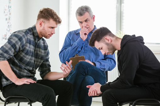 Male Students Discussing Problems By Therapist Stock Photo - Download Image Now