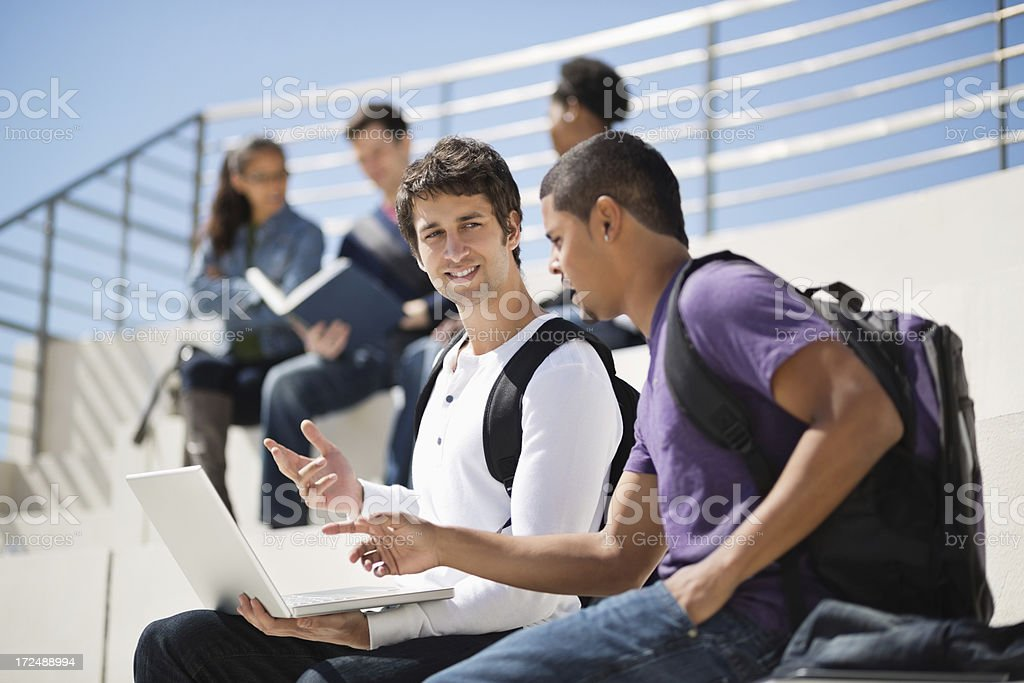 Male Students With Laptop Discussing In Campus royalty-free stock photo