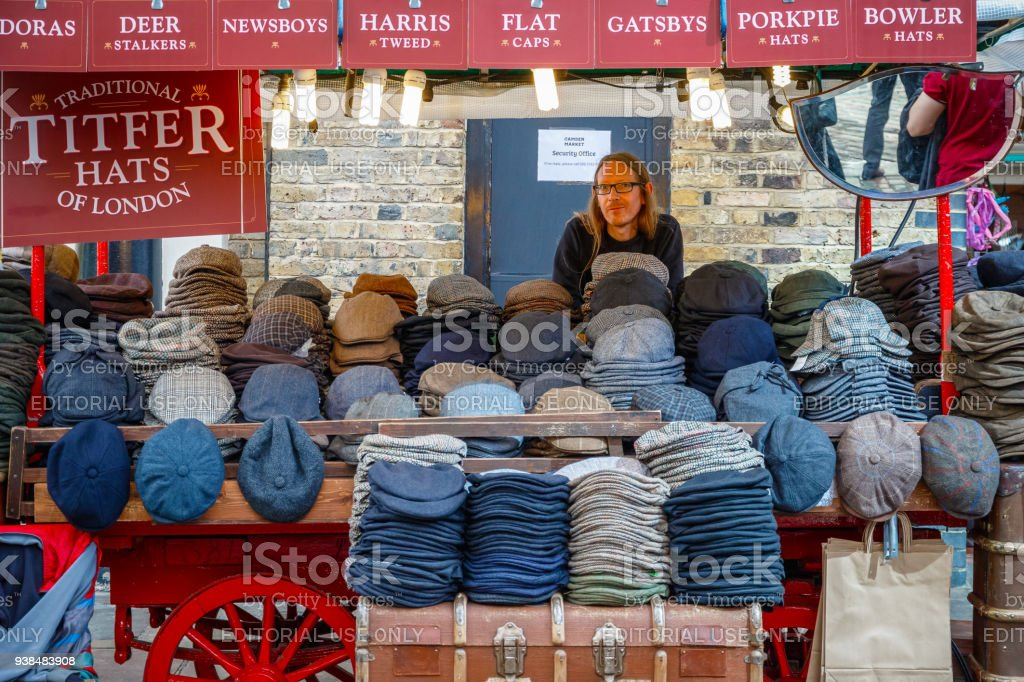 Male stuff selling traditional hats at Camden Market stock photo