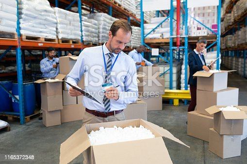 1165376915istockphoto Male supervisor checking stocks in warehouse 1165372348