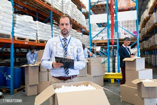 1165376915istockphoto Male supervisor looking at camera while checking stocks in warehouse 1165372393