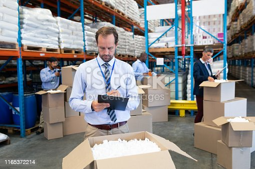 1165376915istockphoto Male supervisor writing on clipboard in warehouse 1165372214