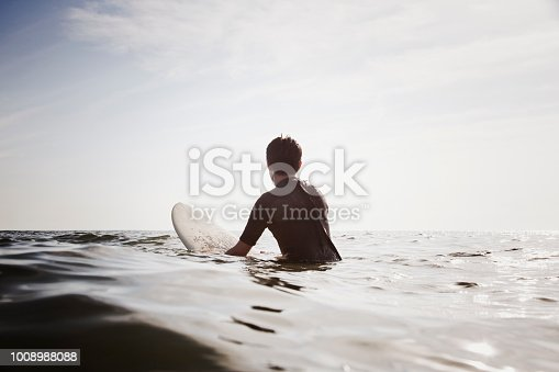 Japanese male surfer with surf board waiting for having a chance to get good waves.