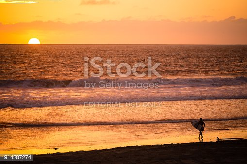 The lone surfer has finished his surfing for the day and is enjoying the sunset. Seal Beach in Orange County, is a popular destination for Southern Californian surfers.