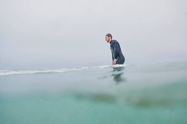 male surfer with his surfboard in the sea at fistral beach, newquay, cornwall on an overcast autumn day. - cornwall stock photos and pictures