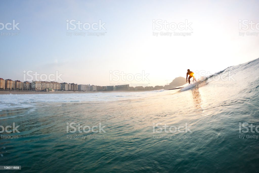 Male surfing on the high waves at sunset stock photo